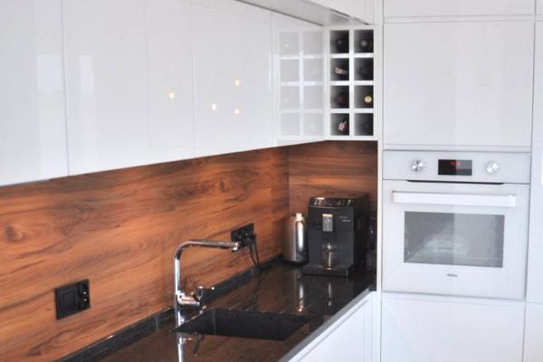 Kuchnia nawymiar Sosnowiec - tanio wykonany projekt kuchni - białe fronty kuchenne, lakierowane, panele naścianach imitujące drewno ibiały piekarnik + półka nawino.