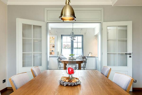 Projekt kuchni zjadalnią isalonem Kraków - projektowanie kuchni wstylu skandynawskim, połączonej zsalonem. Otwierane drzwi oddzielające obie przestrzenie.