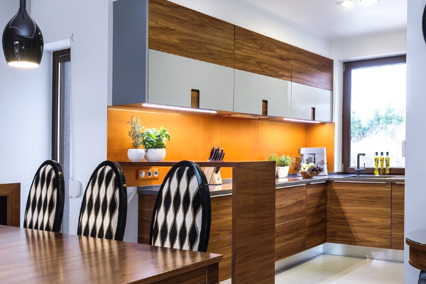 Projekt kuchni zjadalnią isalonem - modna kuchnia biało-brązowa zpomarańczową ścianą istołem wjadalni.