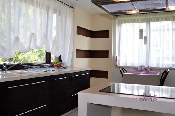 Projekt kuchni zjadalnią imałym salonem - zabudowa wkształcie litery L orazstół wkuchni.