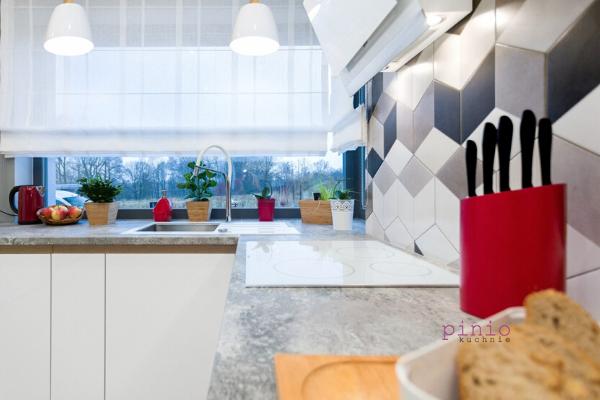 Wąska kuchnia wbloku zwielkiej płyty wkolorach białym iszarym. Granitowy blat wkuchni przezcałą długość ściany, niskie szafki stojące.